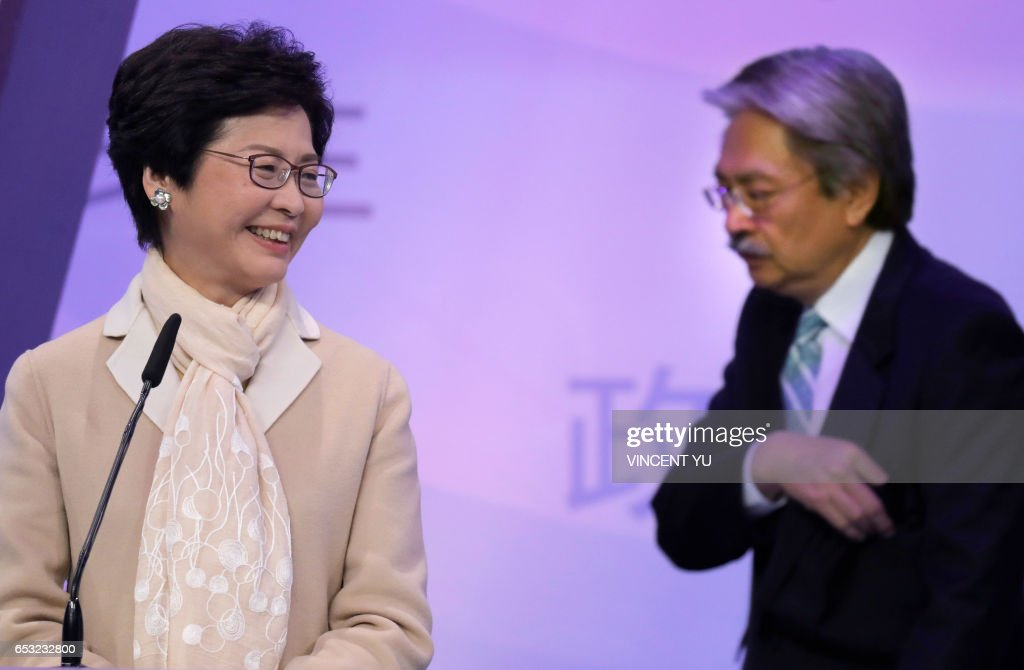 Two of the three Hong Kong leadership candidates John Tsang (R) and Carrie Lam (L) attend the first televised debate at a studio in Hong Kong on March 14, 2017. Hong Kong's three leadership candidates faced off in their first televised debate on March 14 as criticism mounts over a voting process which favours Beijing and bypasses the majority of the electorate. / AFP PHOTO / POOL / Vincent Yu