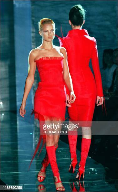 Two of the vermillon dresses trimmed in horsehair over matching legginglike boots that Italian designer Donatella Versace sent out 18 July in Paris...