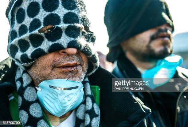 TOPSHOT Two of twelve migrants claiming to be from Iran protest with sewn lips against the dismantling of the southern part of the socalled 'Jungle'...
