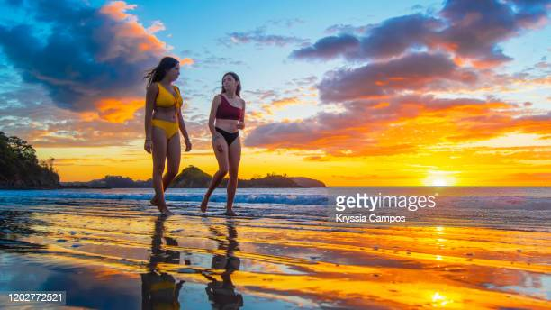 two of young women walking at twilight on a tropical beach in costa rica - guanacaste stock pictures, royalty-free photos & images