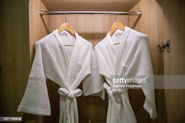 two off white color bathrobes hanging in warmly design closet, room for copy space