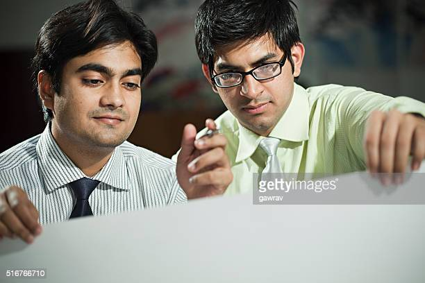 Two office worker observing on a big sheet of paper.