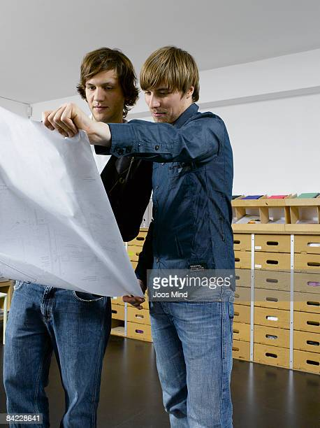 two office workers looking at construction plan