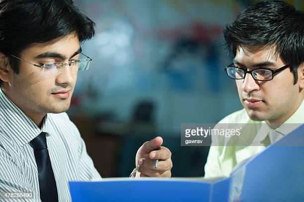 Deux employés examinant fichier ensemble dans leur bureau.
