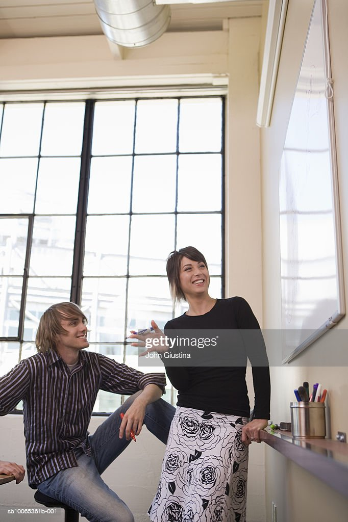 Two office workers standing at whiteboard : Foto stock