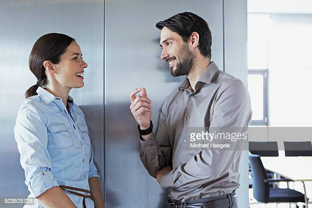 two office workers talking in conference room - flirtare foto e immagini stock