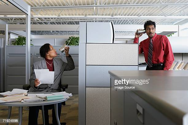 Two office workers using a tin can telephone