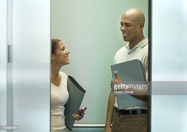 Two office workers with files talking in closing elevator