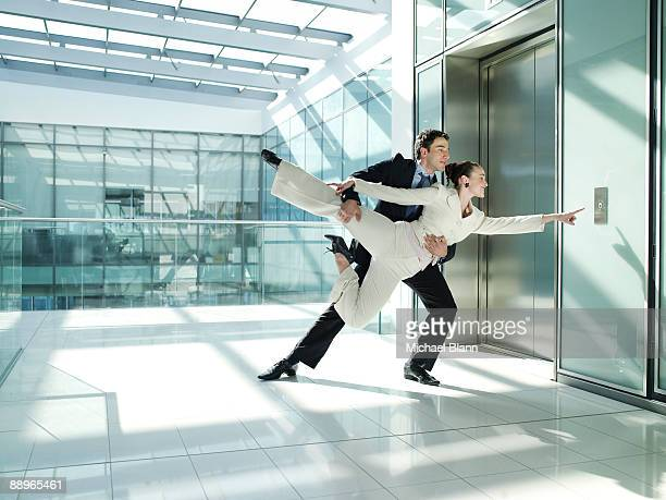 two officemates dancing to open the elevator door - dancer stock pictures, royalty-free photos & images