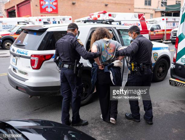 Two officers of the New York Police Department escort a handcuffed woman under arrest to the Emergency Room at the Elmhurst Hospital Center in the...