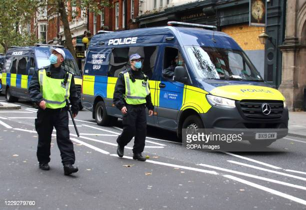 Two officers wearing facemasks with Territorial Support Group van in support, patrol the route of the march. With a number of expected demonstrations...
