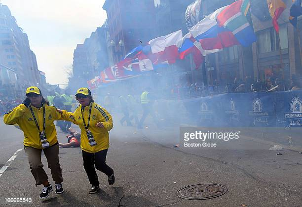 Two officials run away from the first explosion right on Boylston Street at the 177th Boston Marathon April 15 2013