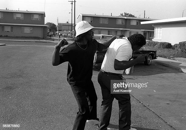 Two OG members of the Grape Street Crips engage in a friendly tussle as they are hang out in their neighborhood The Grape Street Watts Crips are a...