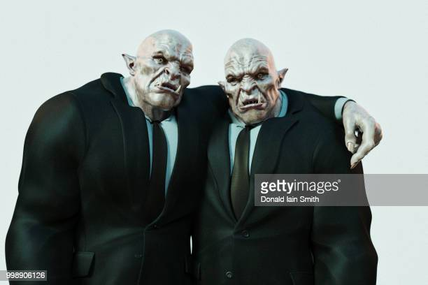 two ogre friends with arm round shoulder and waist - troll stock photos and pictures