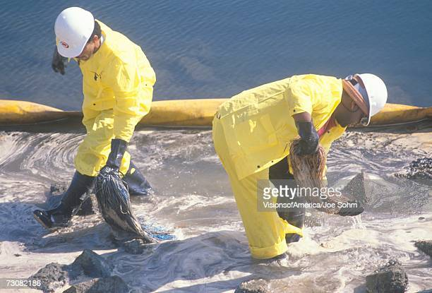 Two oil cleanup workers wade in oily water between a yellow oil barrier and a rocky shoreline clearing up oil with absorbent material after a spill at Orange County, California