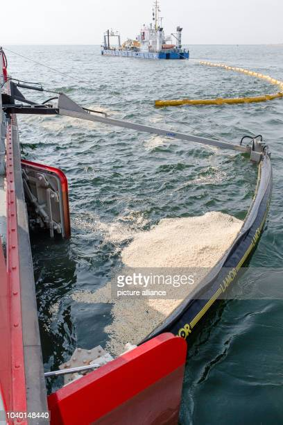 Two oil recovery vessels sail during an exercise with a funnel through a simulated oil carpet made of popcorn before the island Sylt near Hoernum...