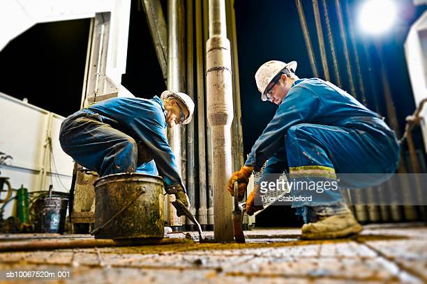 two oil workers working on drilling rig - oil industry stock pictures, royalty-free photos & images