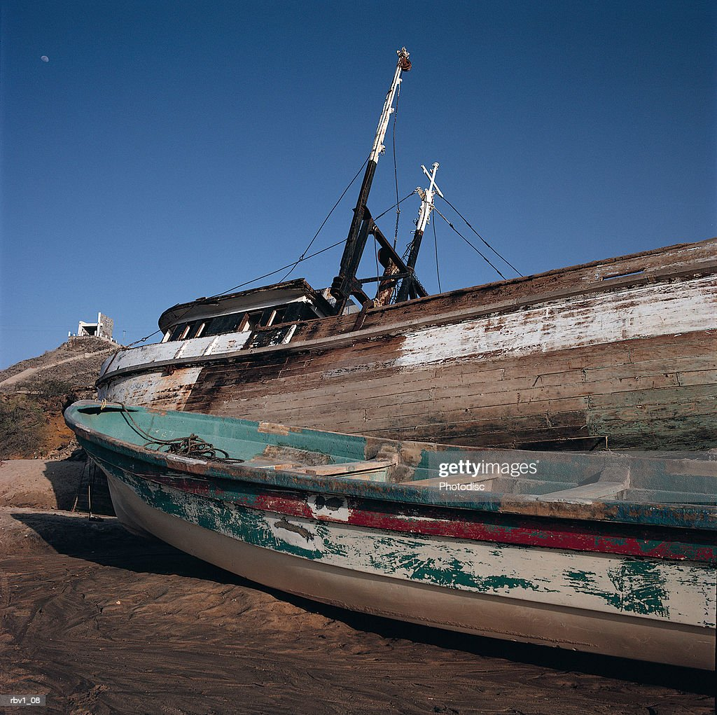 two old abandoned fishing boats line the edge of a shore under a clear blue sky : Foto de stock