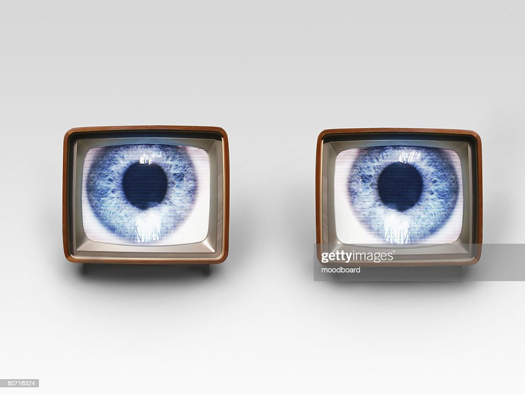Two old fashioned TV sets with blue eyes in studio shot : Stock Photo