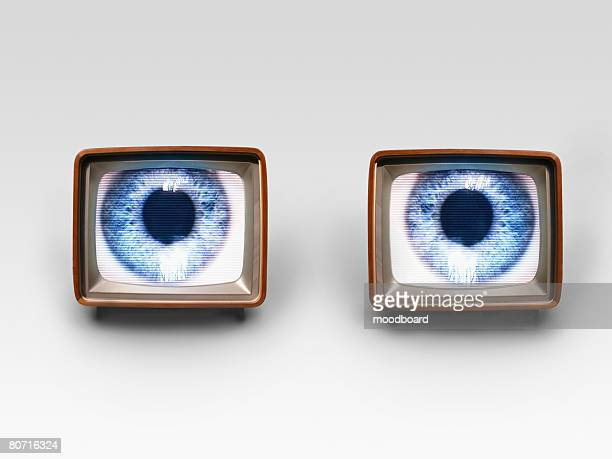 Two old fashioned TV sets with blue eyes in studio shot