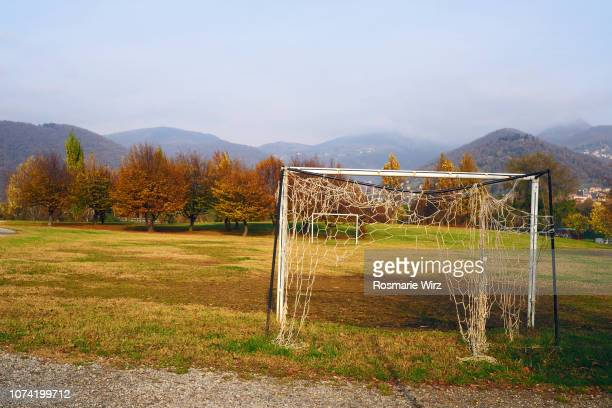 two old  football goals with torn nets - bad condition stock photos and pictures
