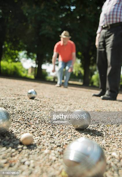 Two old friends playing boule in the park