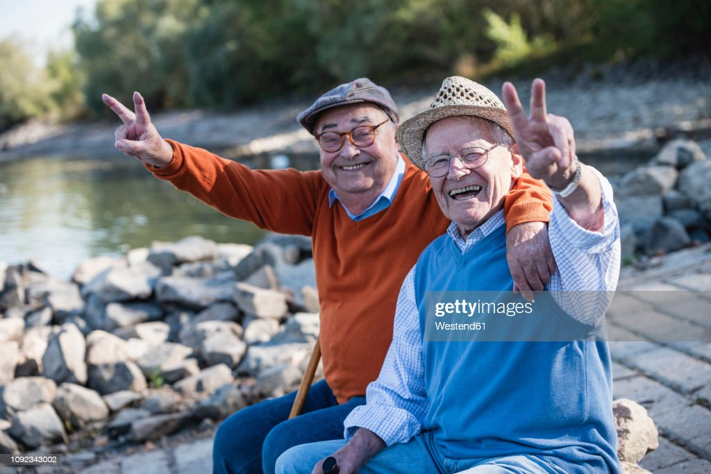 Two old friends sitting by the riverside, having fun : Stock Photo