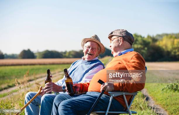 two old friends sitting in the fields, drinking beer, talking about old times - cadeira dobrável - fotografias e filmes do acervo