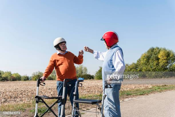 two old friends wearing safety helmets, preparing for a wheeled walker race - respekt stock-fotos und bilder
