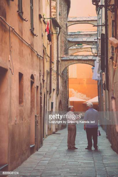 Two old men are talking in the alley of old town in Albenga, Italy.