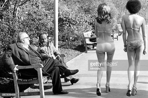 Two old men sitting on a park bench distracted by models in bikini walking past February 1975 7501132005