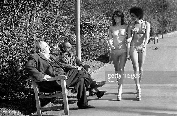Two old men sitting on a park bench distracted by models in bikini February 1975 7501132008