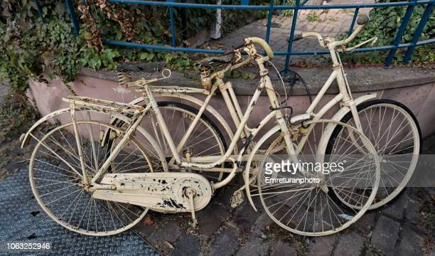 Two old parked and chained bycles.