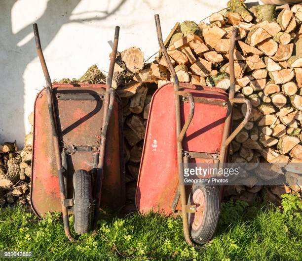 Two old red metal wheelbarrows leaning against pile wood logs in garden Cherhill Wiltshire England UK