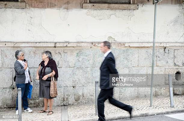 Two old woman discussing on the sidewalk