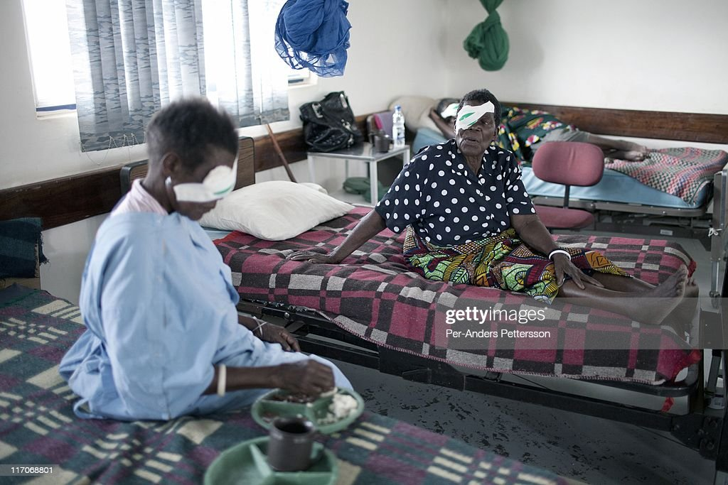 two old women wait for cataract surgery in a ward at the