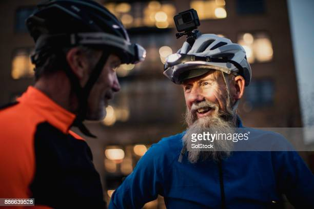 Two Older Cyclists One  Wearing a Helmet Camera at Dusk