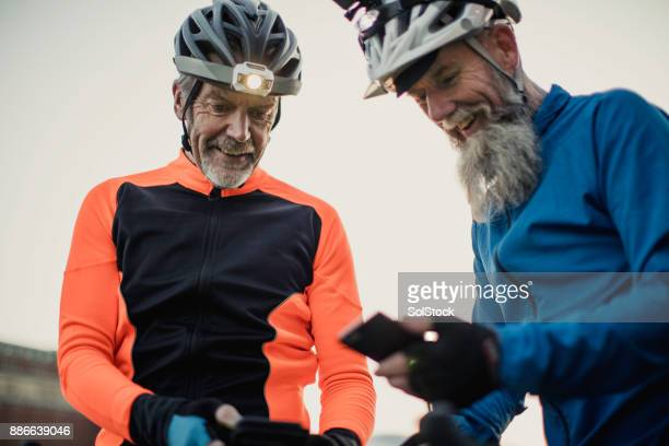 Two Older Cyclists One  Wearing a Helmet Camera Holding a Phone