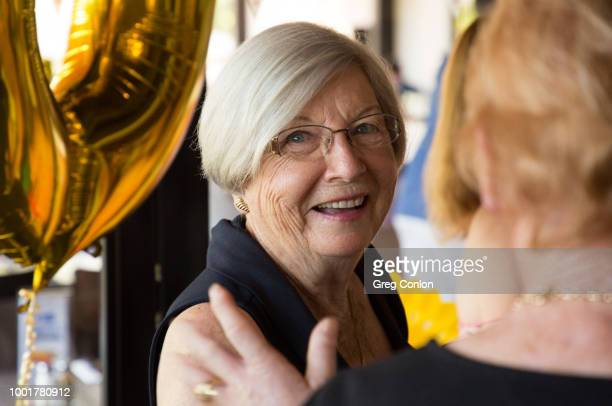 Two older ladies in happy conversation at a birthday party