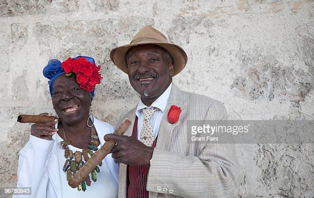 two older people pose with cigars for tourist - cultura cubana foto e immagini stock