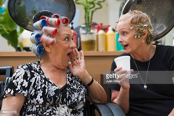 Two older woman gossiping at hair salon