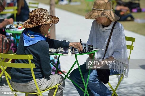 Two older women play chess at a public park