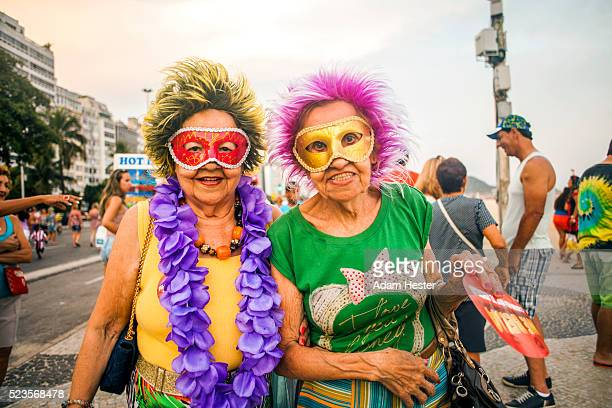Two older women posing for a picture while dressed up on Carnival in Rio De Janeiro.
