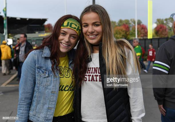 Two opposing fans pose for a photo outside the stadium prior to the start of the game during a college football game between the Washington State...