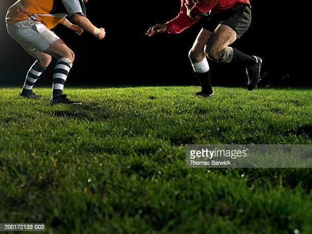 two opposing rugby players, one holding ball, night, low section - ラグビーボール ストックフォトと画像