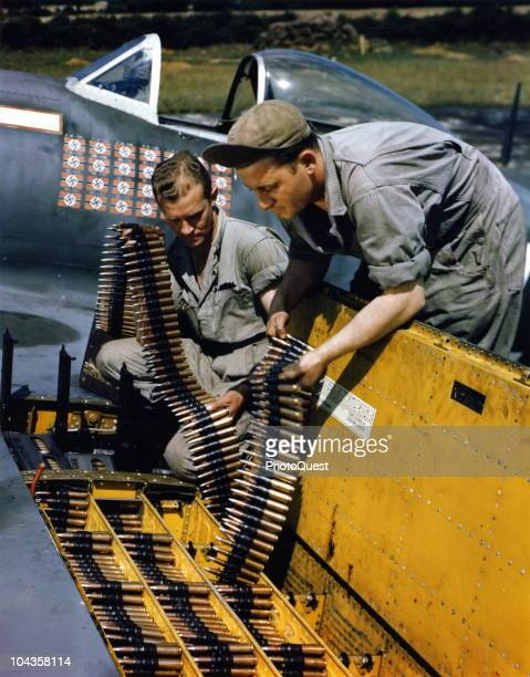 Two ordinance men load 50 calibur cartridge belts into the wing of a Republic P47 Thunderbolt fighter plane at an unspecified base in England...