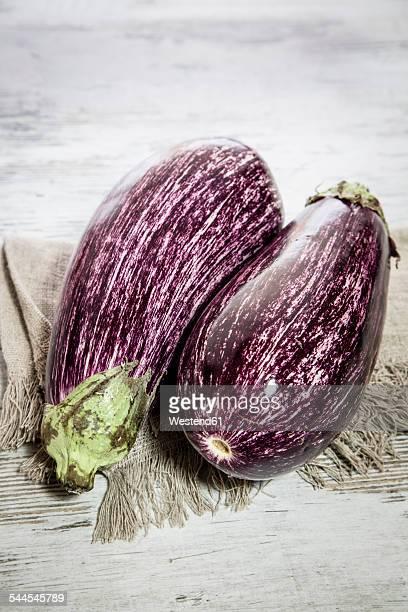Two organic aubergines on cloth
