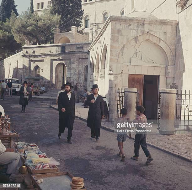 Two orthodox jewish men walk down the Via Dolorosa past the Polish Catholic Chapel marking the third station of the cross in Jerusalem Israel...