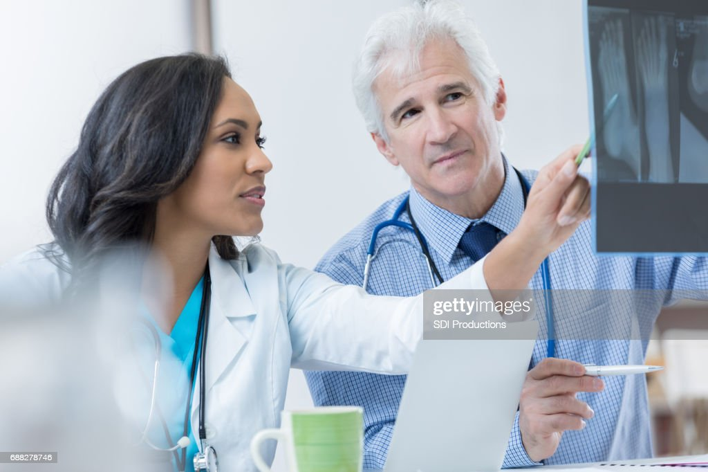 Two orthopedic doctors discuss patient's x-ray : Stock Photo