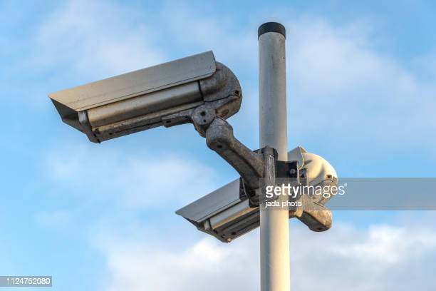 two outdoor security cameras mounted on a pole - defending stock pictures, royalty-free photos & images